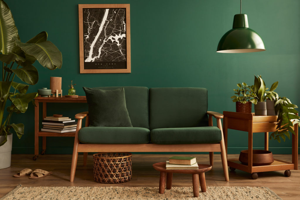 Dunkelgrünes Sofa und Möbelstücke aus dunklem Holz