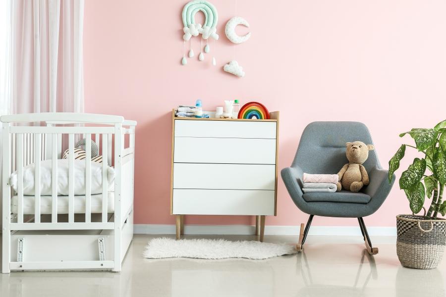 Freundliches Kinderzimmer mit Babybett, Sessel und einer Kommode