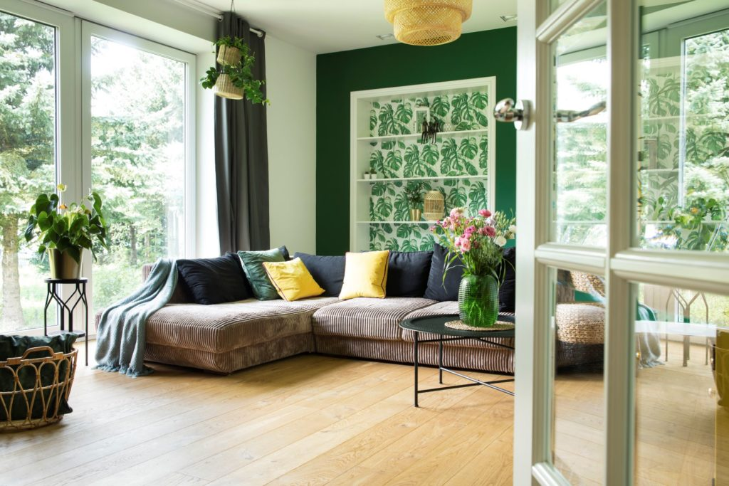 Modernes Kordsofa in einem grünen Wohnzimmer