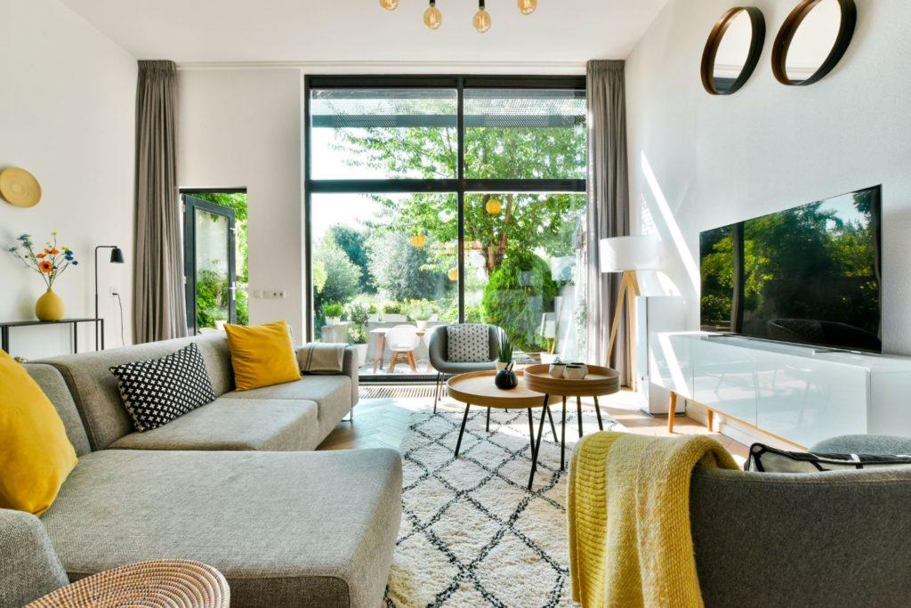 Graues Sofa mit gelben Zierkissen für ein farbenfrohes Wohnzimmer
